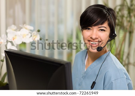 Smiling Attractive Multi-ethnic Young Woman Wearing Headset and Scrubs Near Her Computer Monitor. - stock photo