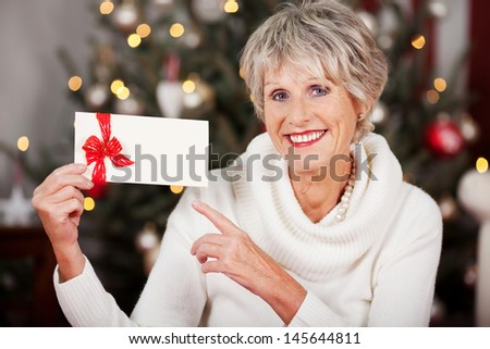 Smiling attractive senior woman pointing to a blank Christmas voucher in her hand as she sits in front of a decorated Christmas tree with lights - stock photo