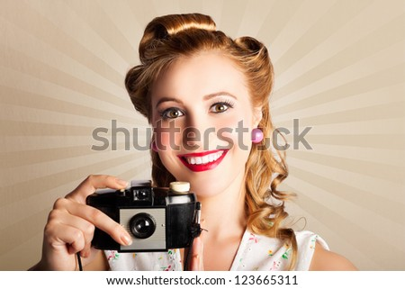 Smiling Attractive Sixties Woman Using A Vintage Photographic Camera While Standing Against A Vintage Flashback Background - stock photo