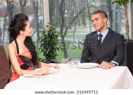 Smiling attractive woman and man having discussion. couple discussing menu at lunch break  - stock photo