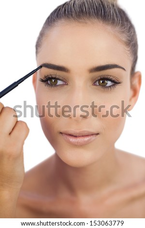 Smiling attractive woman applying make up on her eyebrows on white background - stock photo