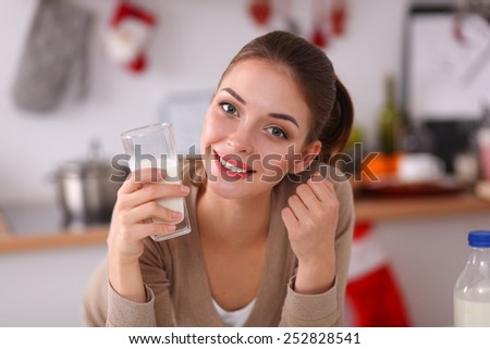 Smiling attractive woman having breakfast in kitchen interior