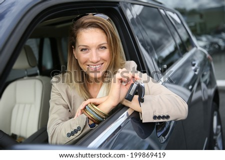 Smiling attractive woman holding brand new car keys - stock photo