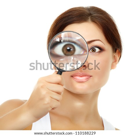 Smiling attractive woman looking through a magnifying glass over white background