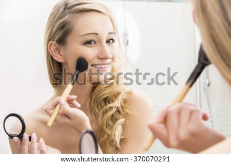 Smiling attractive young blond woman applying blusher to her cheek from a handheld compact using a large cosmetics brush, focus to her reflection in the mirror in a beauty concept - stock photo