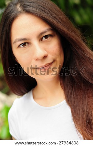 Smiling attractive young brunette woman outdoors - stock photo
