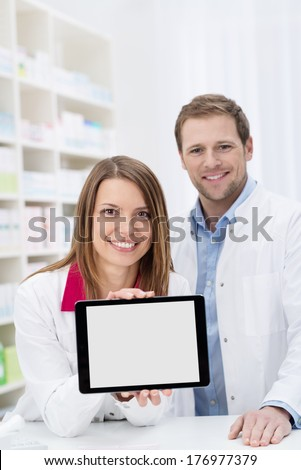 Smiling attractive young female pharmacist displaying a blank tablet with the screen to the camera watched by a male colleague