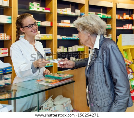 Smiling attractive young female pharmacist serving a senior lady over the counter dispensing her prescription medication