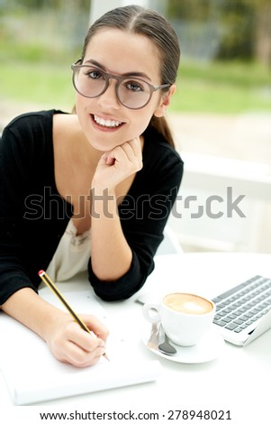 Smiling attractive young female student wearing eyeglasses sitting doing e-learning on a laptop computer writing notes for her classes - stock photo