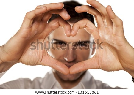 smiling attractive young man makes the heart using fingers - stock photo