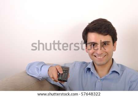 smiling attractive young man watching televison - stock photo