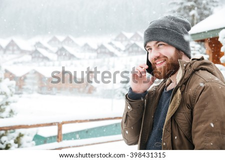 Smiling attractive young man with beard talking on cell phone outdoors in snowy weather - stock photo