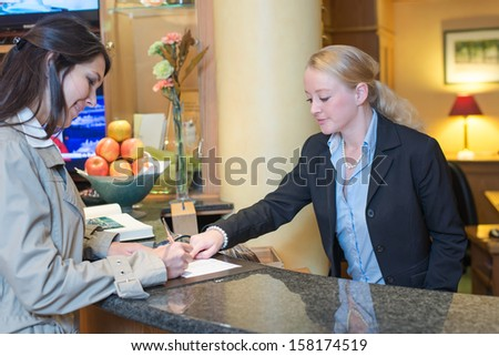 Smiling attractive young receptionist helping a hotel guest check in pointing to information on the form that needs to be completed as they stand at the service desk in the lobby - stock photo