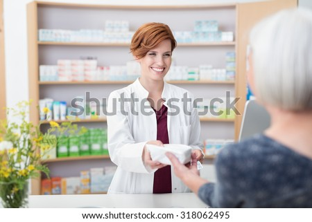 Smiling attractive young redhead pharmacist handing over prescribed medicines to an elderly female patient, view over the clients shoulder of the pharmacist - stock photo