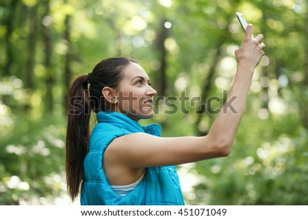 Smiling attractive young running sporty woman macking selfie on the nature, forest, park background in blue sleeveless jacket.Sport. Instagram - stock photo