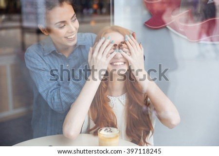 Smiling attractive young woman covered eyes by hands to cheerful redhead girl sitting in cafe - stock photo