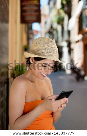 Smiling attractive young woman in a colorful orange summer dress and straw hat reading a sms on her mobile while leaning against a building in a narrow urban street