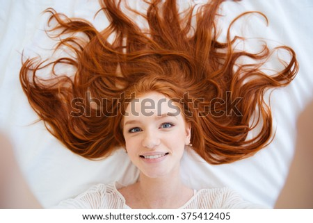 Smiling attractive young woman with beautiful long red hair lying in bed and taking selfie - stock photo