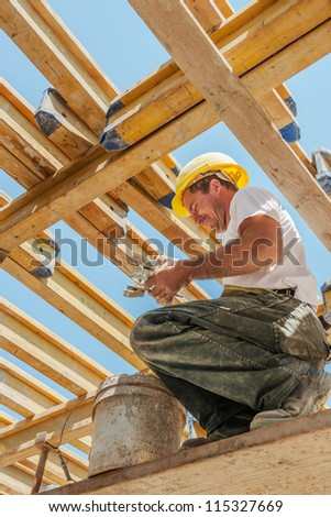 Smiling authentic construction builder working with clamps underneath slab formwork beams - stock photo