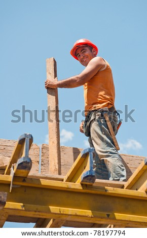 Smiling authentic construction worker with beam standing on top of formwork - stock photo
