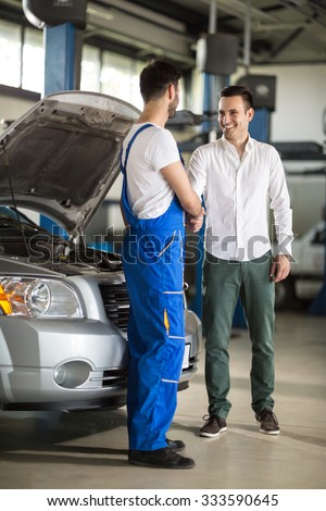smiling auto mechanic and client shaking hands in sevice - stock photo