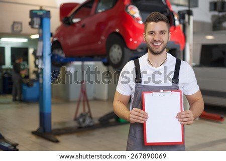 Smiling auto mechanic standing against red car in workshop and holding a clipboard with blank paper sheet - stock photo