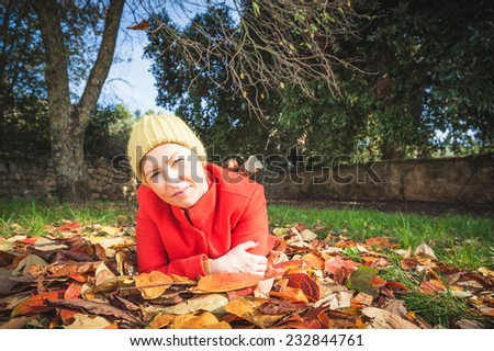 Smiling autumn woman lying on leaves in the park - stock photo
