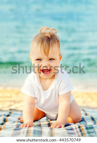 Smiling baby against the sea shore background.