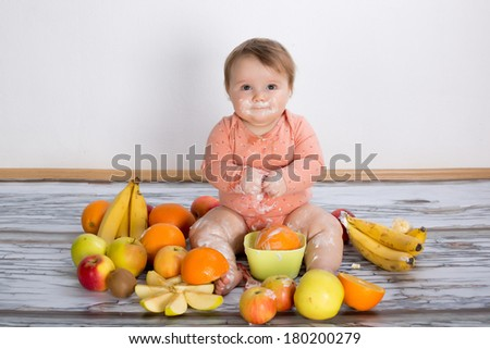 Smiling baby and many kinds of fruit and bowl with yogurt - stock photo