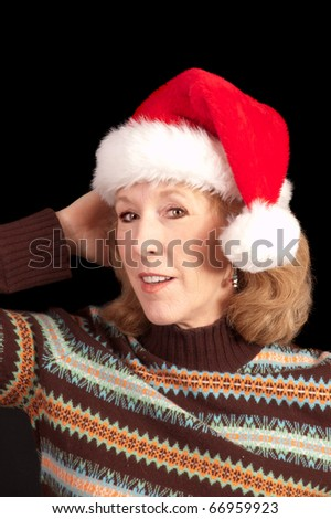 smiling Baby boomer woman with Santa hat on over a black background - stock photo