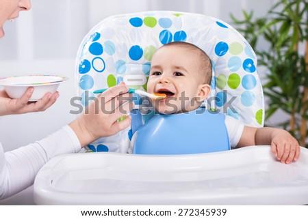 Smiling baby boy enjoy at feeding time in kitchen - stock photo