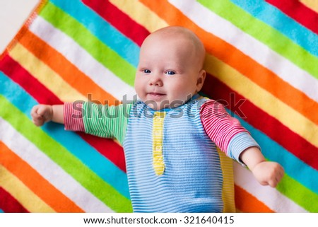 Smiling baby boy in bed. Laughing child on a colorful blanket. Children sleep. Bedding for kids. Newborn napping in bed. Healthy little new born kid shortly after birth. Clothing for kids. - stock photo