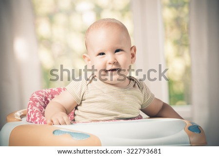 smiling baby boy in the baby walker - stock photo