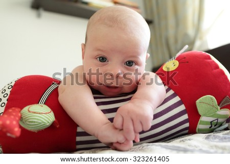Smiling baby boy lying on a crawling roll at home - stock photo