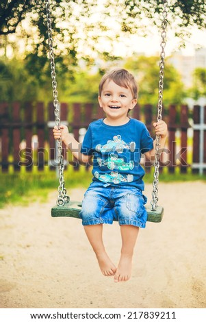 smiling baby boy on a swing - stock photo
