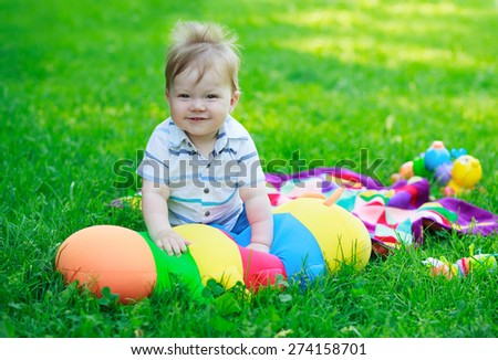 Smiling baby boy on background of toys and grass in park - stock photo