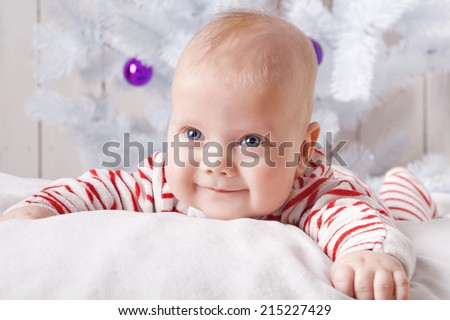 Smiling baby boy on the soft white pillow under the decorated Christmas tree - stock photo