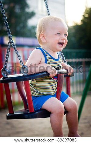 Smiling  baby boy sitting in a swing - stock photo
