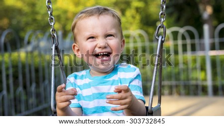 Smiling baby boy swinging in the city park during summer - stock photo