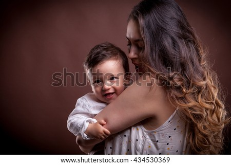 Smiling baby child beeing hold in hands. Motherhood and parenting happiness - stock photo