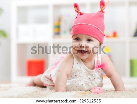 Smiling baby child crawling on nursery room floor - stock photo