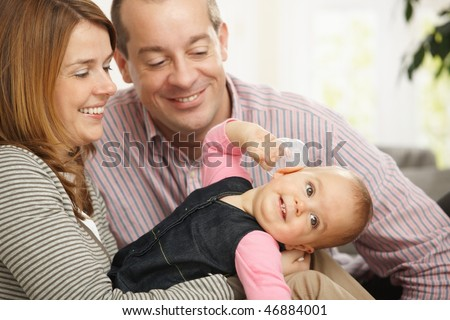 Smiling baby girl held by happy mother, father sitting smiling down at baby at home.