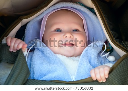 smiling baby girl in a wheelchair - stock photo