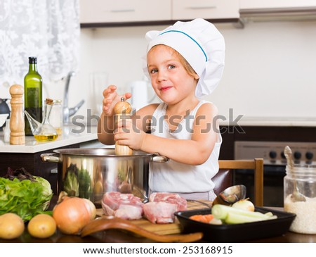 Smiling baby girl in chef�¢??s hat cooking with meat and vegetables at home kitchen