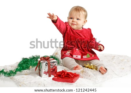 Smiling baby girl in red velvet dress and gray stretch pants reaches up with one arm. She sits near wrapped holiday gifts and green garland. Isolated/cut out, white background, horizontal, copy space.