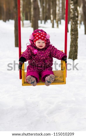 smiling baby girl in winter jacket and hat playing on a swing - shallow DOF - stock photo
