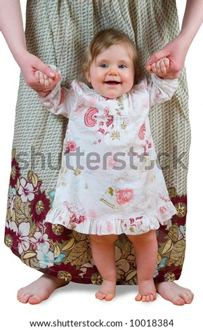 Smiling baby girl learning to walk holding mother's hands - stock photo