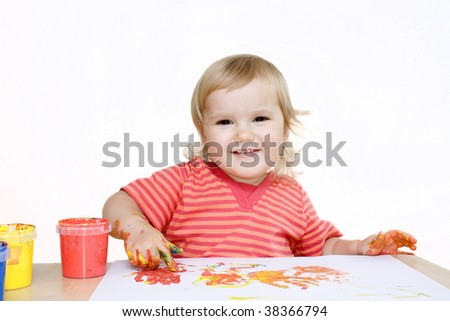 Smiling baby girl painting with a finger