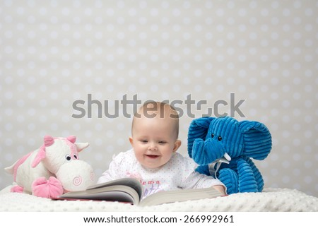 Smiling baby girl reading a book with little toy friends - stock photo