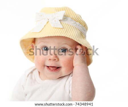 Smiling baby girl showing tongue wearing a yellow hat isolated on white background - stock photo